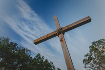 A large wooden cross against a blue sky.