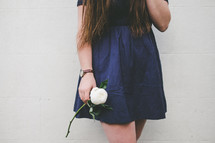 a young woman holding a white flower in her hand