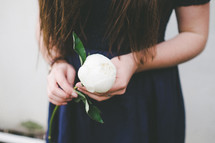 woman's hands holding a white flower