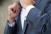 a groom with Avenger cuff links adjusting his bow tie