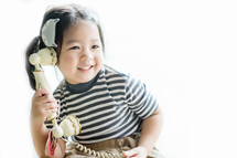 a toddler girl on an antique phone