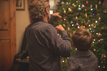 a father and son decorating a Christmas tree