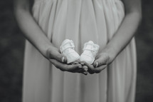 pregnant woman holding baby shoes