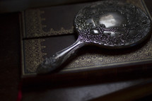 An antique, silver mirror laying on a book.