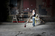 boy with a push broom sweeping in an alley