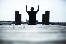 man sitting on a dock with hands raised