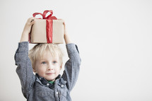 A child holding a Christmas gift.