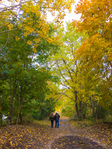 couple walking on a dirt road in fall