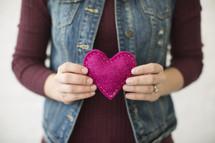 a woman holding a pink felt heart