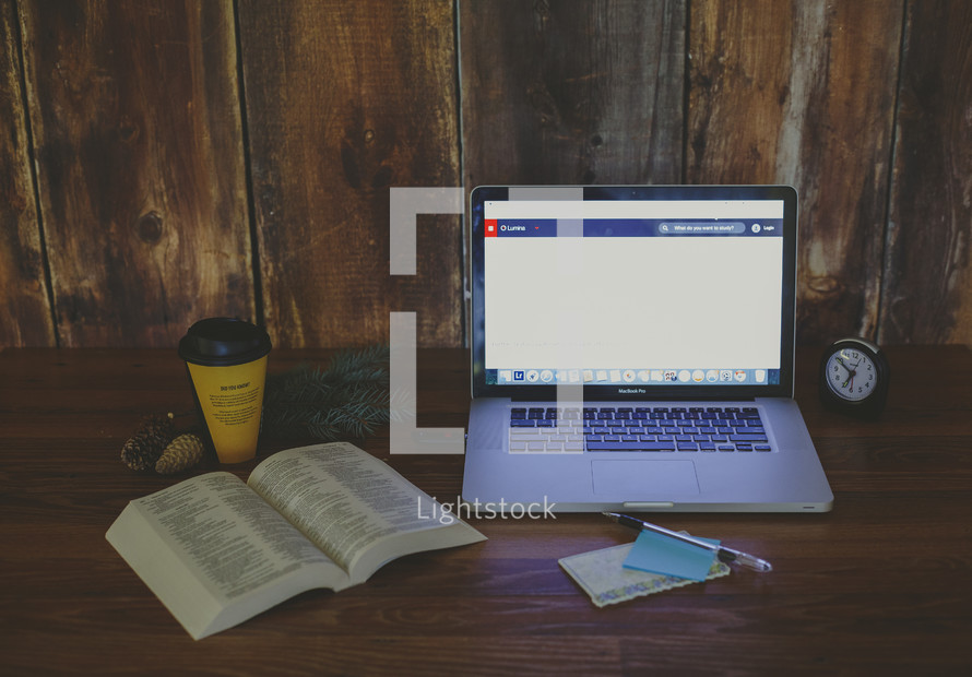 open Bible, coffee cup, and laptop on a desk