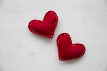 red felt hearts on a white wood table.