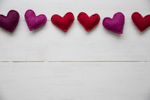 border of felt hearts on white wood background.