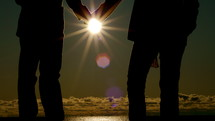 Silhouette of couple holding hands in the moonlight at the beach.