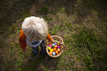Child carrying a basket of Easter eggs while standing in the grass.