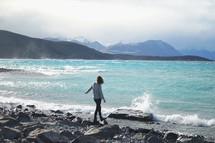 woman walking on rocks along a coastline