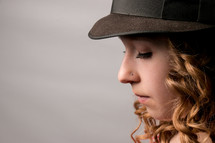 A girl in a hat with a nose piercing.
