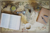 open Bible, mug, reading glasses, pen, journal, and ink on a world map