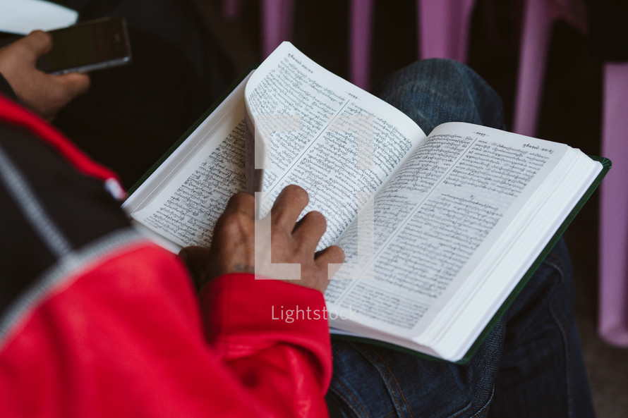 person reading a Bible during a worship service