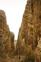 a woman standing in a canyon surrounded by jagged rock peaks