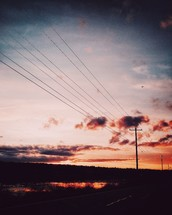 power lines and rural road at sunset