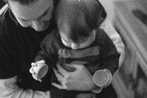 father holding his toddler son who is playing with a plastic Easter egg