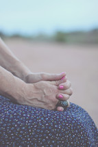 praying hands in a woman's lap