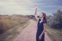 woman standing on dirt road with hand raised praising God
