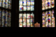 candle and a stained glass windows in a church