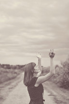 woman standing on a dirt road with hands raised praising God