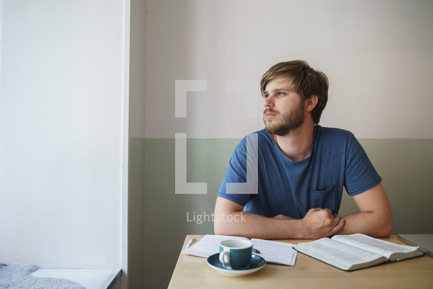 a man sitting at a table with a Bible and journal