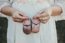 a pregnant mother holding baby girl shoes