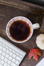 steaming mug of coffee and computer keyboard in fall