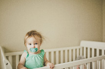 toddler girl with a pacifier in a crib