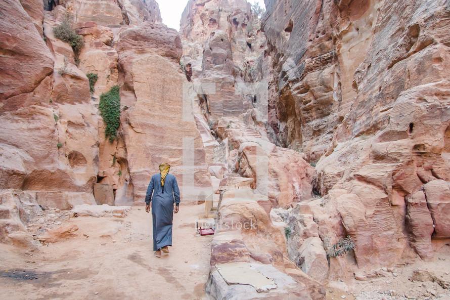 a man walking in the desert in the middle east in jordan.