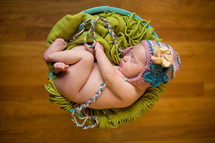naked newborn girl in a hat in a basket