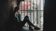 woman sitting in a window with bars