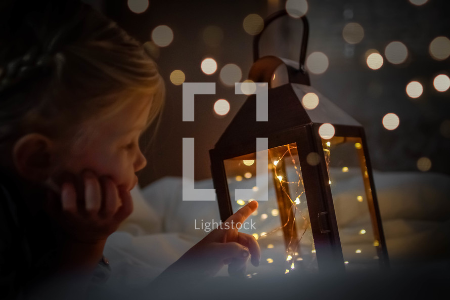 a child looking at a lantern