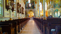 A historic church view of the center aisle and pews lined on each side of the aisle and walls adorned with stained glass windows, sculptures and three dimensional artwork dating back from the early 1800s.
