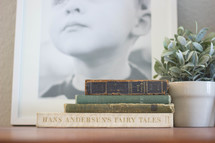 stacked old books, framed photo, and house plant on a table