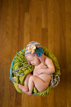 naked newborn in a basket wearing a hat