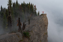 arms outstretched as a person stands on a high rock lookout