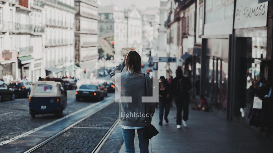 woman walking down a city sidewalk
