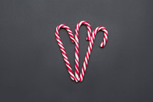 three candy canes on a gray background