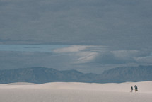 A couple treks through the dunes of White Sands National Monument, searching for a spot to rest.