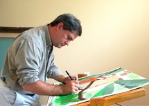 A male Artist paints intently at his easel working on a new painting.