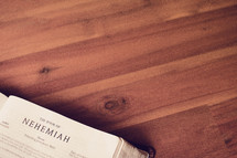BIble on a wood floor opened to Nehemiah