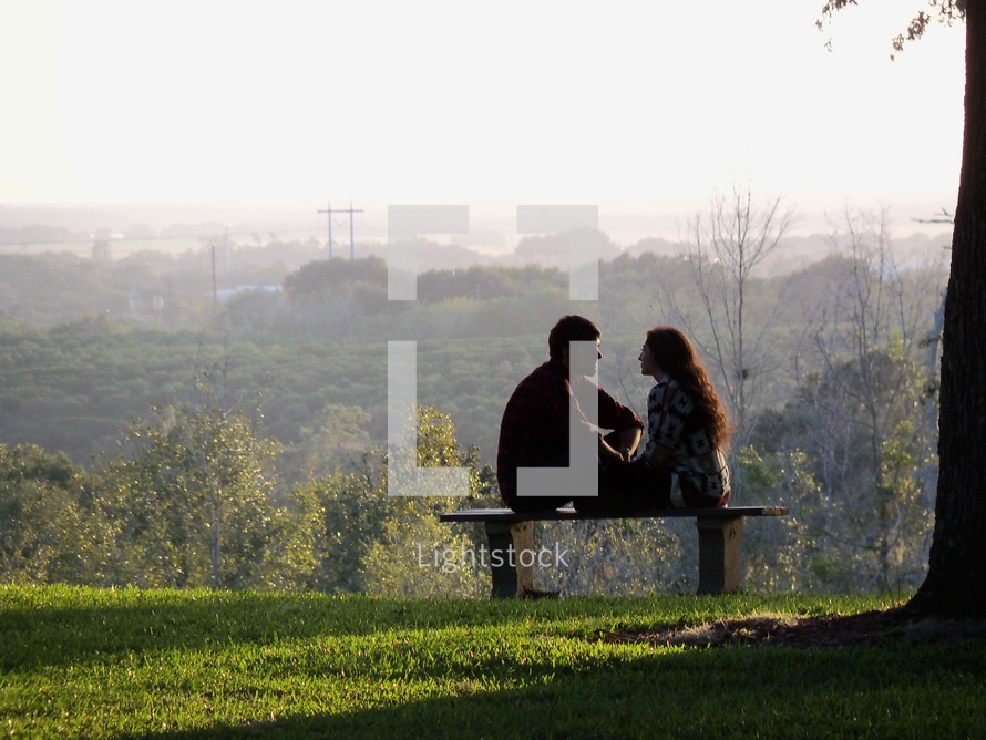 A young couple (man and woman) sit together on a park bench while the sun sets around then in  park with green grass.