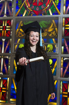 graduate holding her diploma in front of a stained glass window