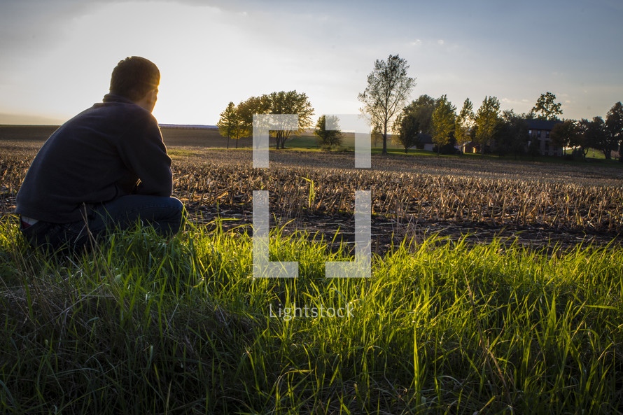 man sitting in a freshly plowed field