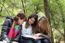 teen girls reading together outdoors